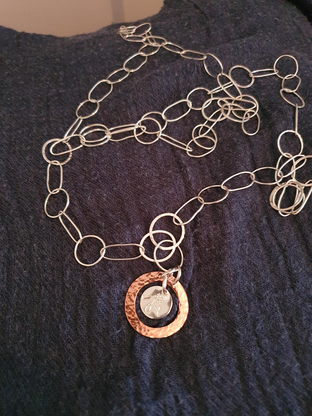 Long, elegant necklace with a 'joy' pendant