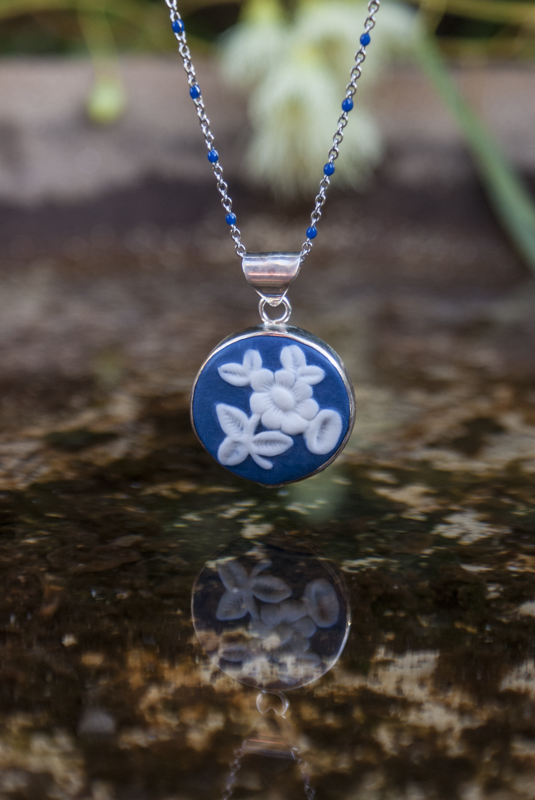 Hand carved porcelain set in silver cameo pendants