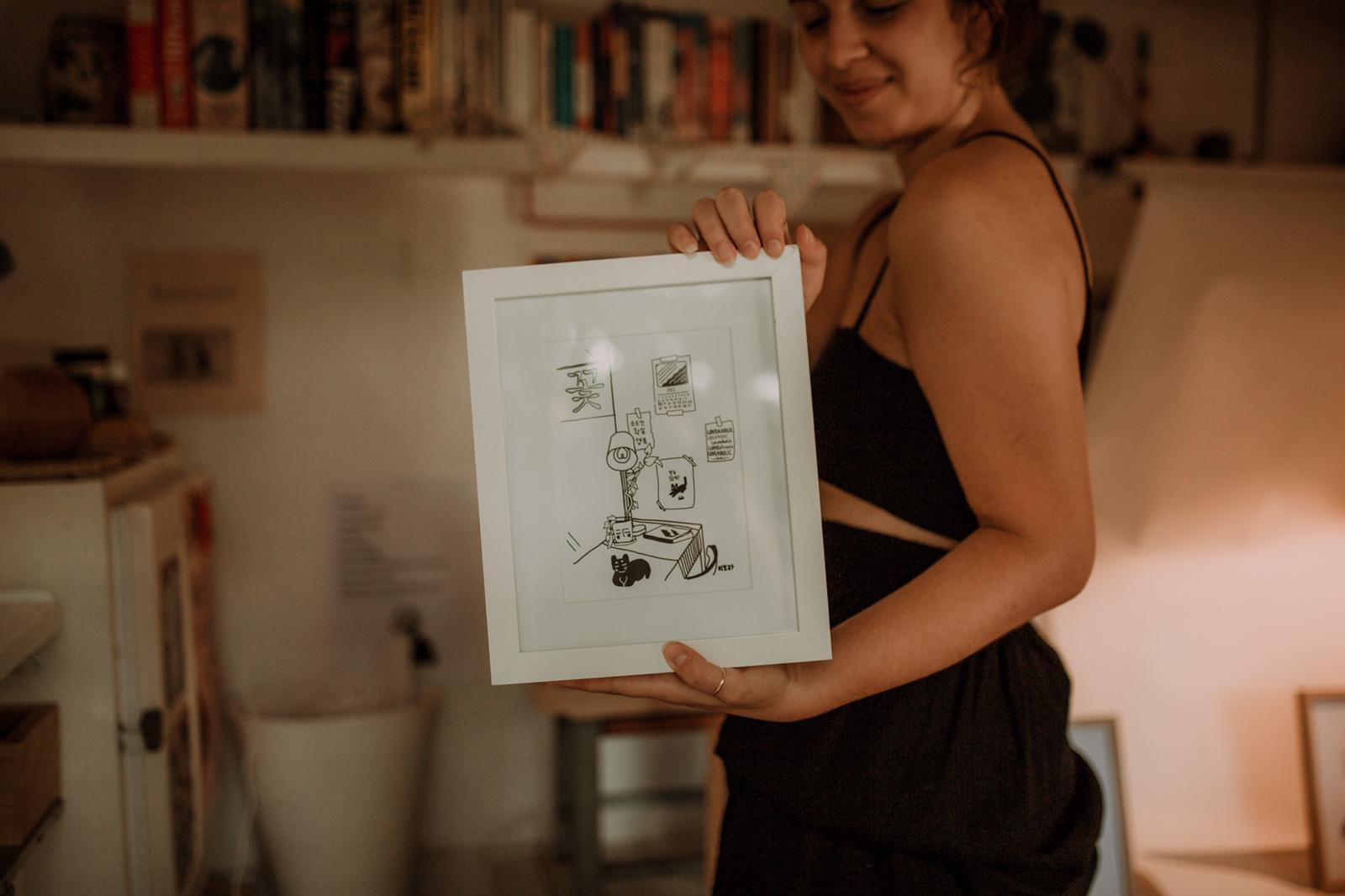 "Kikitsa Draws, inside caravan, holding framed ""Cat Resting in Flower-café"""