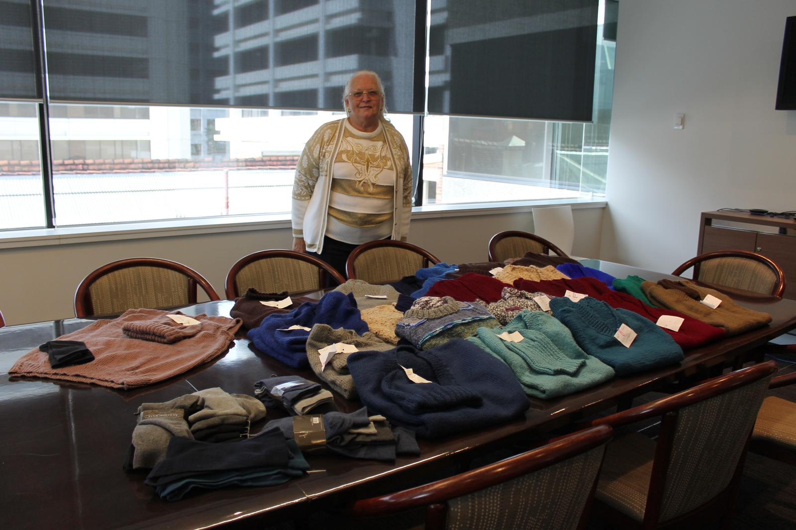 A volunteer poses with pullovers she & a team knitted for in need veterans.